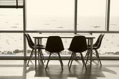 Modern studio med den tomma skrivbord- och exponeringsglasfasaden med havsikt inget kopiera avstånd tabell arkivbilder