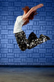 Modern style dancer jumping. Against blue brick wall Royalty Free Stock Photos