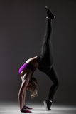 Modern style dancer performs acrobatic exercise Royalty Free Stock Image