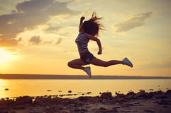 Modern style dancer posing in mid air on beach. Modern style dancer jumping high posing in mid air on beach at sunset royalty free stock image