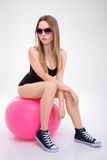 Modern style dancer posing on pink fitball Stock Photo