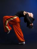 Modern style dancer woman performing. On dark background Stock Photos