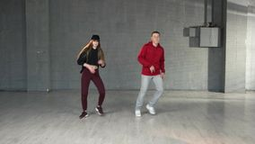 Modern style dancers performing hip-hop. Couple of skillful teenagers dancing contemporary dance in studio stock video footage