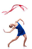 Modern style dancing girl. Studio picture of young caucasian blond girl in blue dress which is dancing with red flying cloth. modern style. isolated on white Stock Images
