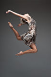 Modern style dancing girl. Studio picture of young caucasian blond girl in gray dress which is flying against dark background. modern style Stock Image