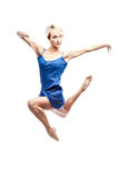 Modern style dancing girl. Studio picture of young caucasian blond girl in blue dress which is jumpimg and looking away. modern style. isolated on white Stock Images
