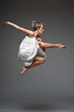 Modern style dancing girl. Studio picture of young caucasian blond girl in white dress which is flying against dark background. modern style Stock Photos