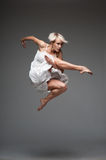 Modern style dancing girl. Studio picture of young caucasian blond girl in white dress which is flying against dark background. modern style royalty free stock photography