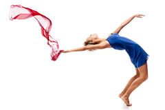 Modern style dancing girl. Studio picture of young caucasian blond girl in blue dress which is dancing with red flying cloth. modern style. isolated on white Stock Photography