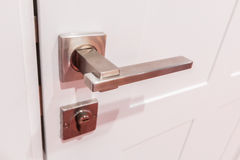 Modern style door handle. On natural wooden door Stock Photography