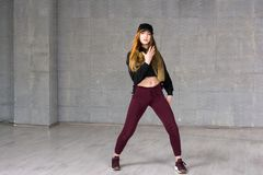 Modern style female dancer. Young woman wearing black cap and sneakers dancing hip-hop dance on grey studio background. Skillfull and talented youth stock images