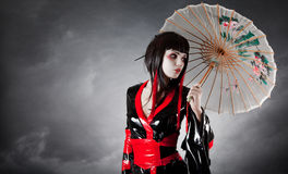 Modern style geisha in fetish kimono. With umbrella, studio shot stock photography