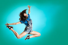 Modern style happy girl dancing on fresh blue background. Hip Hop dancer jumping concept. Royalty Free Stock Photos