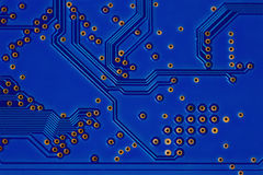 Modern style hardware technology concept with blue circuit board. Macro view electronic chip soldering paths and trace Stock Photos