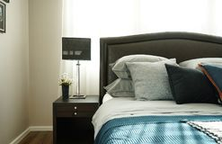 Modern style interior bedroom with pillows. Modern classic style interior bedroom with pillows and black reading lamp on bedside table Royalty Free Stock Photography