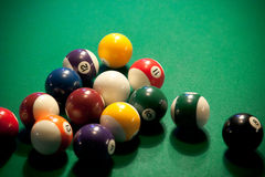 Modern-style pool balls. Already broken apart, waiting for the next player on a green cloth fabric pool table Royalty Free Stock Photography