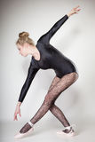 Modern style woman ballet dancer full length on gray Stock Images