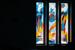 Modern styled stained glass windows. In church, close up view. Mid range view Royalty Free Stock Photo