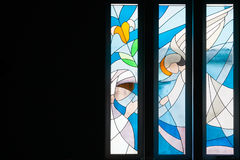 Modern styled stained glass windows. With predominantly blue colors, in church, with angels, mid range view Royalty Free Stock Images