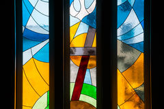 Modern styled stained glass windows. With predominantly blue and yellow colors, in church, with cross and dove symbols, close up view Stock Image