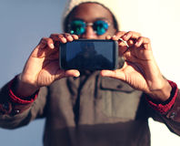 Modern stylish african man makes selfie, screen front view. Technology and people concept - modern stylish african man makes selfie, screen front view royalty free stock image