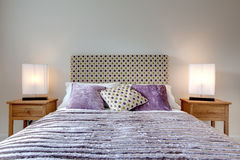 Modern stylish bed. Modern bed dressed with fashionable brightly coloured cushion and quilt, lamps and oak side tables Stock Photos