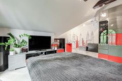 Modern stylish bedroom with TV. Modern stylish bedroom in red and gray with big TV royalty free stock image