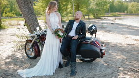 Modern stylish biker wedding. Tatooed young bride and groom in black leather jacket pose to photographer outdoor near the motorcycle stock footage