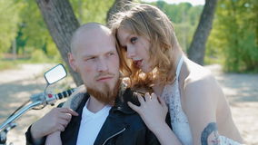 Modern stylish biker wedding. Tatooed young bride and groom in black leather jacket pose to photographer outdoor near the motorcycle stock video