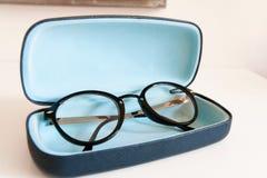 Modern stylish fashionable elegant black eyeglasses in blue leat Royalty Free Stock Photos