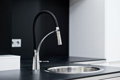 Modern stylish faucet in the design kitchen. Modern stylish faucet in the black and white design kitchen royalty free stock photo