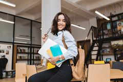 Modern stylish image of smart brunette young woman with laptop on table in library. Smiling to camera, playing with. Black glasses, great success, hard-working stock photography