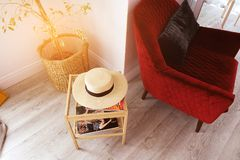 Modern stylish interior, on the coffee table is a straw hat, next to a red chair and a houseplant. Design concept royalty free stock images