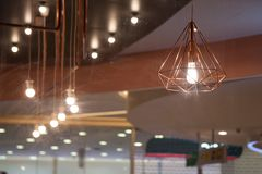 Modern and stylish light bulbs In the restaurant. By Take a shoot from oute through the glass into the shop royalty free stock image