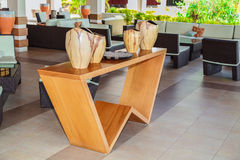 Modern stylish lobby bar interior with closeup view of natural wood stand table and gorgeous beautiful decorated vases Royalty Free Stock Images