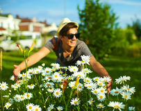 Modern stylish man in casual cloth in hat near flowers Stock Photography