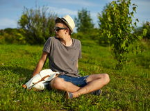 Modern stylish man in casual cloth in hat. Portrait of young attractive modern stylish man in casual cloth in hat in glasses sitting in the park in green grass Royalty Free Stock Images