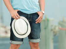 Modern stylish man in casual cloth with hat. Tourism vacation and fashion concept. Modern stylish man in casual cloth holds white hat outdoor Stock Images