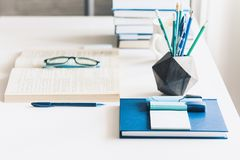 Modern stylish office work place with open book, glasses, office supplies and books, desk work concept in white and blue colors.  royalty free stock images