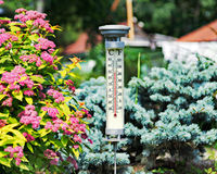 Modern stylish outdoor thermometer in summer garden. Royalty Free Stock Images
