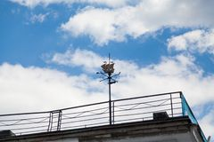 Modern stylish wind vane with high spike. Flat weather vane in the form of a ship on a high spire against a blue cloudy sky stock images