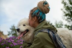 Modern stylish young girl with dreadlocks on her head hugs and kisses her beloved dog snow-white Samoyed. royalty free stock photography