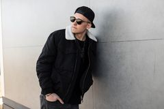 Modern stylish young hipster man in a stylish black jacket in a fashionable cap in trendy dark sunglasses in vintage gray jeans. Posing near a gray concrete royalty free stock photo