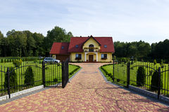 Modern suburban house. Elegant modern suburban house with a parked car and gardens. Poland architecture Stock Image