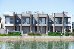 Modern Suburban House. Typical facade of a modern town suburban house near the pond  at noon Royalty Free Stock Images