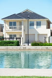Modern Suburban House. Typical facade of a modern town suburban house near the pond  at noon Royalty Free Stock Photography