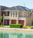 Modern Suburban House. Typical facade of a modern town suburban house near the pond  at noon Royalty Free Stock Photo