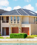 Modern Suburban House. Typical facade of a modern town suburban house near the pond  at noon Royalty Free Stock Photos