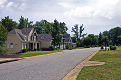 Modern Suburban Neighborhood. A street scene of modern homes and landscaped yards Royalty Free Stock Photos