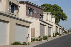 Modern Suburbia. Medium Density modern housing, with garage doors, street, tree and blue sky stock photo